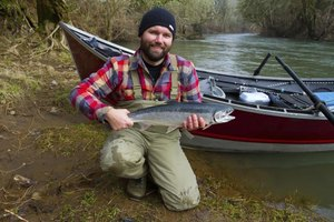 A fisherman holding a steelhead in front of his boat and a river.