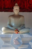 A statue of the Buddha is the centerpiece of a Buddhist shrine in a temple room.