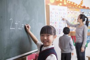 A schoolgirl calculates a math equation on the chalkboard.