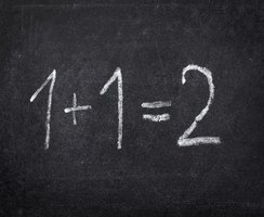 Close-up of addition problem written on chalkboard.