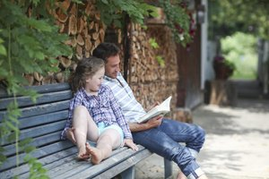 Father and daughter reading a book on a bench.