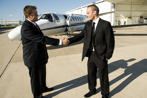 Two businessmen shaking hands in front of a commercial jet.