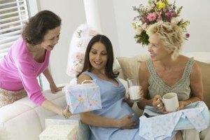 Woman handing gift over to expectant mother at baby shower.
