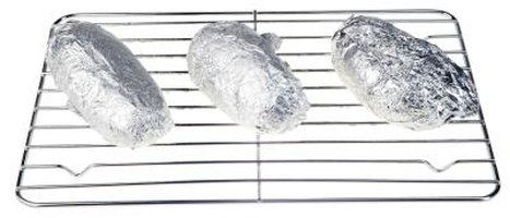 Baked potatoes can be cooked on the grill wrapped in aluminum foil.
