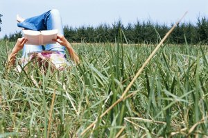 Woman reading book in grass field