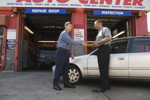 Panel beater shaking hands with customer at car repair shop.
