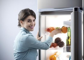 Woman taking food out of a fridge.