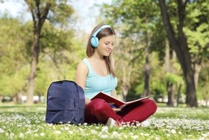 Student wearing headphones while reading book