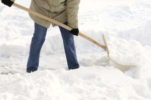 A close-up of a woman shoveling snow.