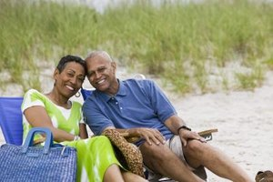 A mature couple sitting on chairs at the beach.
