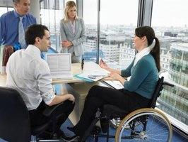 Businesswoman in wheelchair holding office meeting