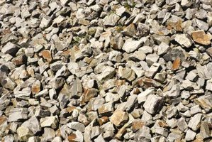 A layer of crushed stone is laid on top of an even and compacted subgrade.