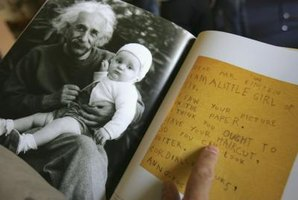 A photo of Albert Einstein with a baby and a letter in a booklet.