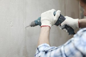 Man with gloves drills into a wall.