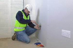 An electrician installing a wall socket.