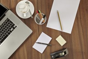 A desk is organized with a lap top, stationary and notepads all in their individual places, spaced out evenly across the desk.