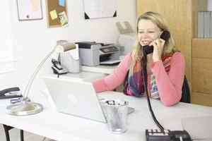 A woman on the telephone working from her home office.
