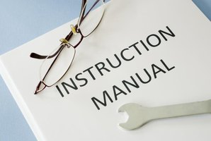 Instruction manual documents underneath glasses and a wrench.
