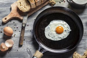 A fried egg in a skillet alongside fresh bread on a cutting board, peppercorns and sea salt.