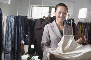 A female sales associate sorts through inventory at a clothing store.