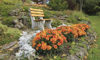Autumn flowers blooming in a rock garden with a bench.
