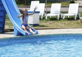 A young girl goes down a slide into a swimming pool.