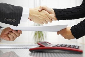 Business colleagues shake hands as they exchange a contract