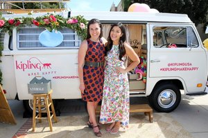 Two businesswomen promoting their products from a retro van on a college campus.