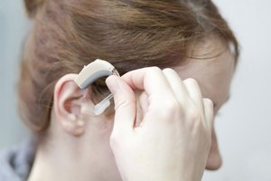 Young woman putting in hearing aid