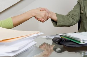 A close-up of a handshake and paperwork on a desk.