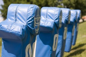 A row of tackling and blocking dummies at a footbal practice.