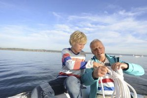 A retired couple is working together on a sailboat.