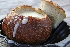 Mussel soup served in a bread bowl on a scalloped plate.