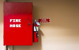 Fire extinguisher and fire hose on wall.