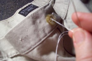 Sew a button onto the waistband of a pair of pants.