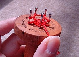 A knitting spool is a simple tool that can be made with an old wooden spool and some small nails.