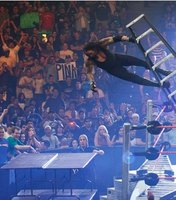 The Undertaker is about to fall through a set of four breakable tables.
