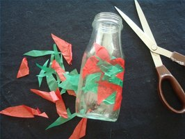 Covering a small recycled glass jar with tissue cuttings to make a vase