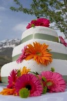 There are a variety of ways to decorate a wedding cake using artificial flowers