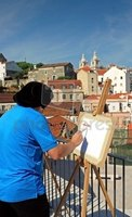 An inspired artist at an easel paiting a cityscape.