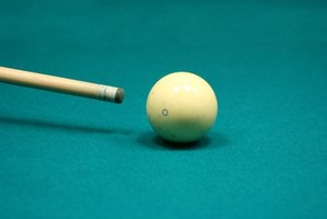 A pool cue tip approaches the cue ball.