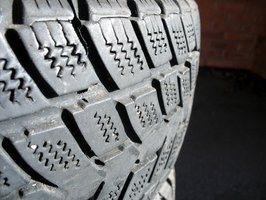 Car tires have tiny cracks on the rubber.