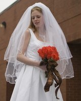 Traditional bride in white dress and veil, holding a bouquet of red roses.