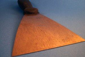 Use a wide drywall knife to scrape damaged texture and paint.