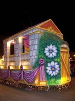 One of the ways to decorate a parade float is to cover it with paper flowers.