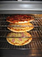 Multiple pizzas can be cooked in one oven due to its rack system.