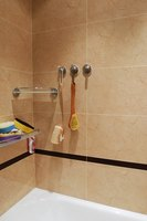 Remove caulk from a fiberglass shower stall with a caulk remover.