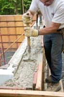 Cement footings are built first with the retaining wall built after the footing sets.
