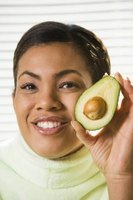 A woman displays an avocado.