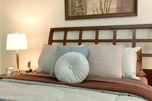 Recreate the look of a tufted pillow on the headboard with fabric and covered buttons.